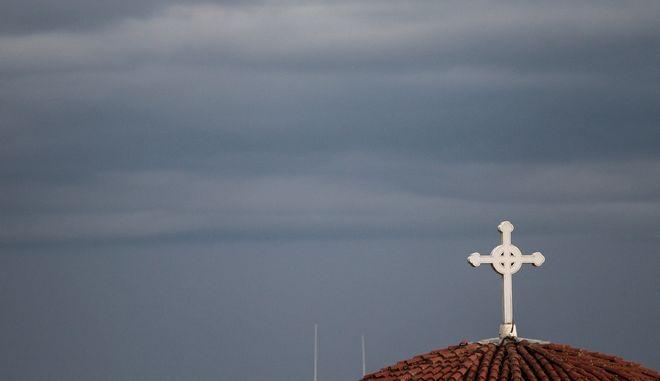 Σύννεφα πάνω από τον σταυρό που βρίσκεται στον  τρούλο του Μητροπολιτικού Ναού του Αγίου Νικολάου στην πόλη των Τρικάλων