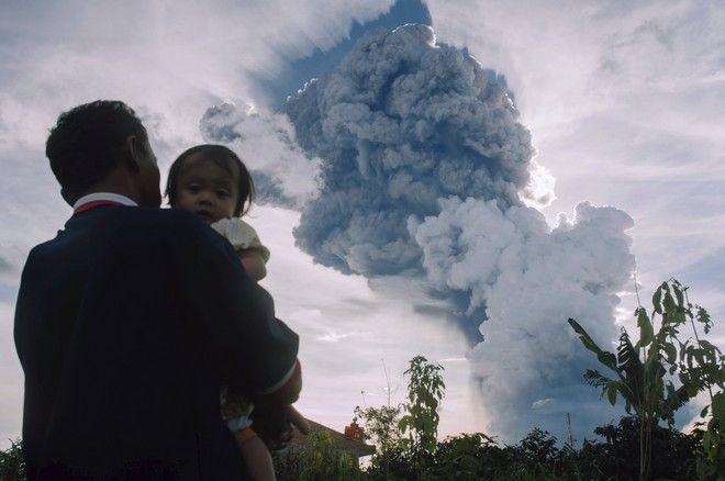 Άνδρας κρατά το παιδί στην αγκαλιά του με φόντο την ηφαιστειακή τέφρα στην Ινδονησία