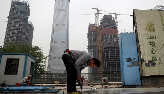 In this Sunday, April 16, 2017 photo, a worker assembles an aluminum platform outside a construction site at the Central Business District of Beijing. China's economic growth ticked higher to 6.9 percent in the first quarter of the year, according to the latest figures.  The official data released Monday, April 17, 2017, show that the world's second-biggest economy grew at a slightly faster pace in the January-March period compared with the previous quarter's 6.8 percent expansion (AP Photo/Andy Wong)