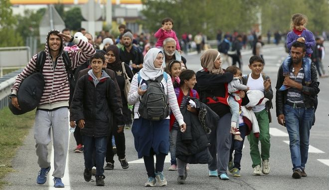 FILE - In this Sept. 11, 2015 file photo migrants walk on the highway A4 toward Vienna after crossing the Hungarian-Austrian border near Nickelsdorf, Austria. Ahead of Austrian national elections Sunday, Oct. 15, 2017, the question is less whether the country will swing rightward under the next government and more about how sharp that turn will be, with voters set to reward two major parties that have exploited fears of immigration and Islam. (AP Photo/Ronald Zak, file)