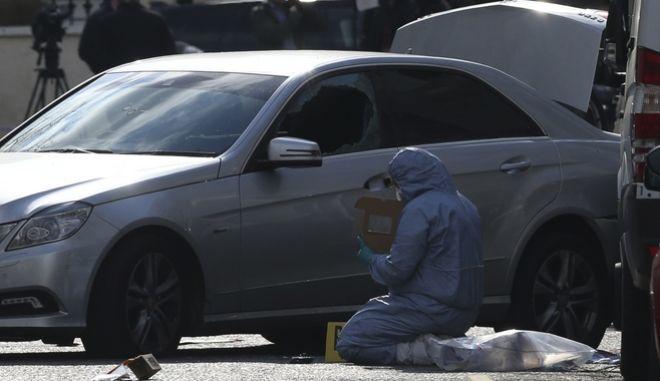 Αστυνομικός εξετάζει αυτοκίνητο. Φωτογραφία αρχείου.
