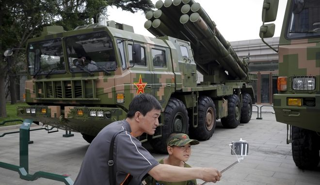 A man helps a child to take selfie near a multiple missiles launcher vehicle on display at the military museum in Beijing, Thursday, July 27, 2017. The museum showcasing some Chinese latest weapons to commemorate the 90th anniversary of the founding of the People's Liberation Army on Aug. 1, 2017. (AP Photo/Andy Wong)