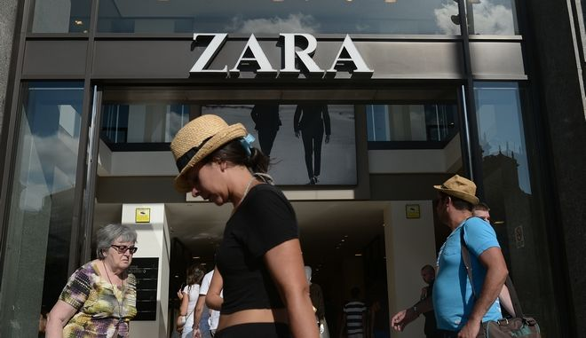 People walk past a Zara store in Barcelona, Spain, Wednesday, Aug. 27, 2014. Spanish fashion retailer Inditex says it has withdrawn a children's shirt which triggered an outcry from people who said it was reminiscent of the clothes Jews were made to wear at Nazi concentration camps. (AP Photo/Manu Fernandez)