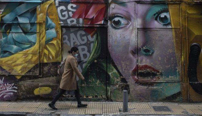 Γυναίκα με μάσκα περπατά στο κέντρο της Αθήνας