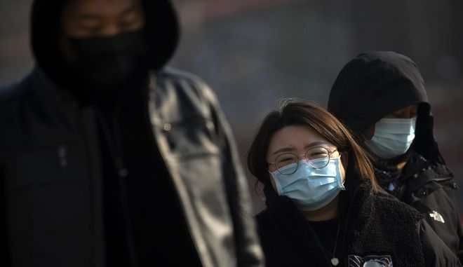 People wearing face masks to protect against the spread of the coronavirus walk across an intersection in Beijing, Wednesday, Jan. 20, 2021. China is now dealing with coronavirus outbreaks across its frigid northeast, prompting additional lockdowns and travel bans. (AP Photo/Mark Schiefelbein)