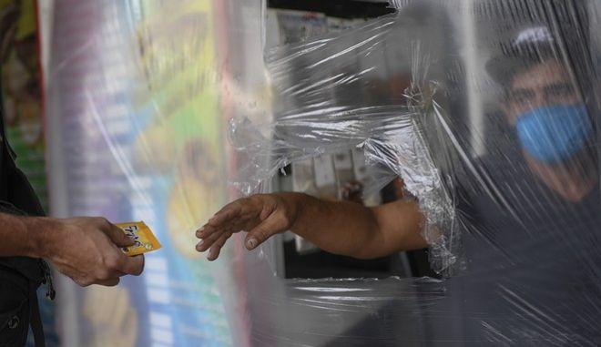 Πληρωμή πίσω από πλαστική κουρτίνα στο Καράκας της Βενεζουέλας ελέω κορονοϊού