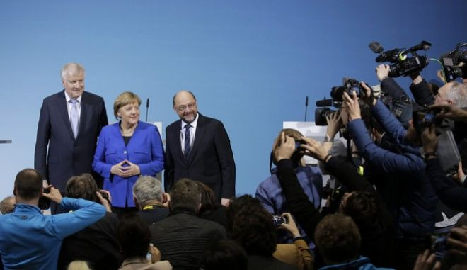German Chancellor Angela Merkel is flanked by Bavarian governor Horst Seehofer, left, and Social Democratic Party Chairman Martin Schulz as they pose for a photo after the exploratory talks between Merkel's Christian Democratic block and the Social Democrats on forming a new German government in Berlin, Germany, Friday, Jan. 12, 2018. (AP Photo/Markus Schreiber)