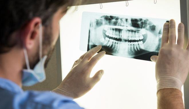 Οδοντίατρος κοιτάζει ακτινογραφία