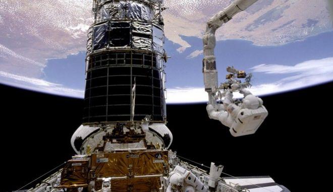 Κατά την πρώτη αποστολή συντήρησης στο Hubble Space Telescope φαίνονται οι αστροναύτες καθώς εργάζονται για την επιδιόρθωση του κυρίως κατόπτρου του τηλεσκοπίου