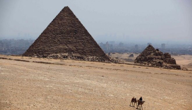 A man rides a camel past Khufu pyramid, the largest of pyramids at the historical site of the Giza Pyramids, near Cairo, Egypt, Tuesday, Aug. 27, 2013. Tourism in Egypt has dropped following unrest surrounding the July 3 popularly backed military coup that ousted President Mohammed Morsi. (AP Photo/Jon Gambrell)