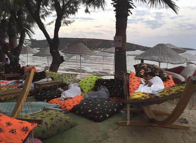 A man sleeps on the beachfront after spending the night outdoors following an earthquake in Bitez, a resort town about 6 kilometers (4 miles) west of Bodrum, Turkey, Friday, July 21, 2017. A powerful earthquake struck Turkey's Aegean coast and nearby Greek islands, sending frightened residents running out of buildings they feared would collapse and into the streets. (AP Photo/Ayse Wieting)