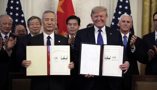 Ο Ντόναλντ Τραμπ και ο Λιου Χε κατά την υπογραφή της εμπορικής συμφωνίας στον Λευκό Οίκο
