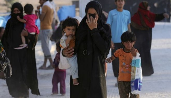 A Syrian family who fled the battle between U.S.-backed Syrian Democratic Forces (SDF) and the Islamic State militants from Raqqa city, arrive at a refugee camp, in Ain Issa town, northeast Syria, Monday, July 24, 2017. The U.S. military is supporting local Syrian forces in a campaign to drive IS from Raqqa. (AP Photo/Hussein Malla)