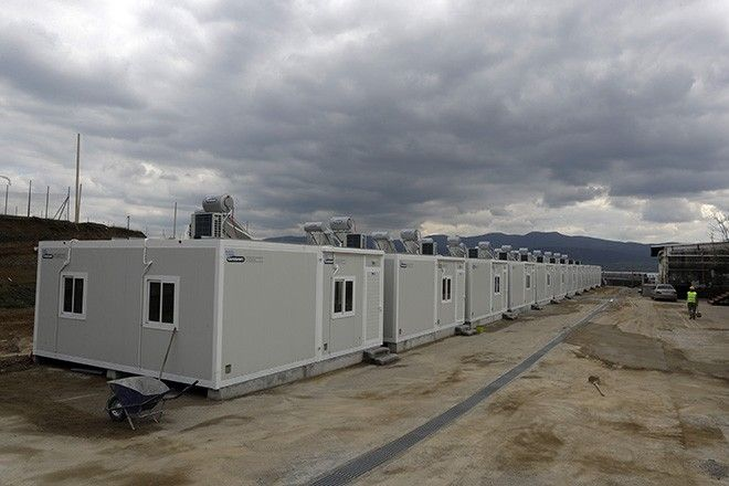 A worker walks next to container houses at a new refugee camp in the town of Thiva, about 90 kilometers (56 miles) north of Athens, on Tuesday, March 14, 2017. The old textile factory will host 700 people and will open for the refugees and migrants in the next days. Over 62,000 refugees and migrants are stranded in Greece after a series of Balkan border closures and a European Union deal a year ago with Turkey to stop migrant flows. (AP Photo/Thanassis Stavrakis)
