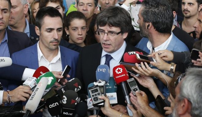 Catalan President Carles Puigdemont, centre, speaks to the media at a sports center, assigned to be a polling station by the Catalan government and where Puigdemont was originally expected to vote, in Sant Julia de Ramis, near Girona, Spain, Sunday, Oct. 1, 2017. Scuffles earlier erupted as voters protested as dozens of anti-rioting police broke into a polling station. (AP Photo/Francisco Seco)