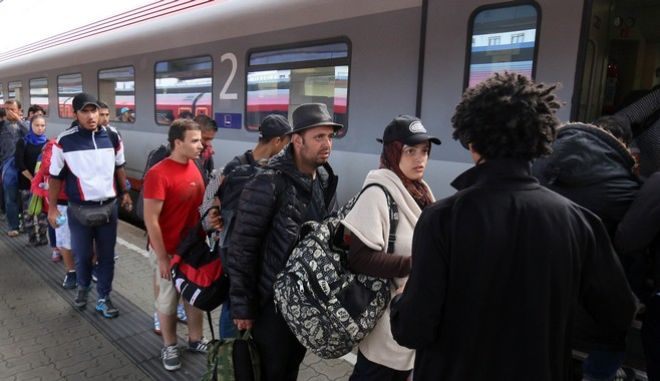 Migrants and refugees board  a train from Vienna to Salzburg at the Westbahnhof train station in Vienna, Saturday Sept. 19, 2015. (AP Photo/Ronald Zak)