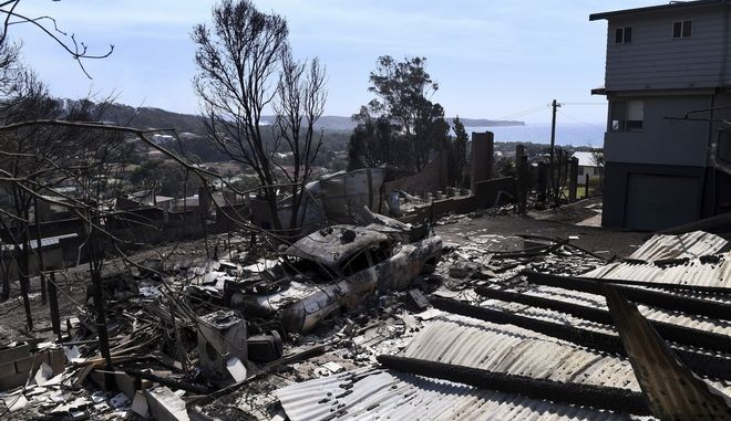 Debris from destroyed homes and a burnt out car lays on the ground in town of Tathra, Australia, Monday, March 19, 2018, following a wildfire. More than 70 homes and businesses had been severely damaged or destroyed by a fire that started in woods around midday on Sunday. (Dean Lewins/AAP Image via AP)