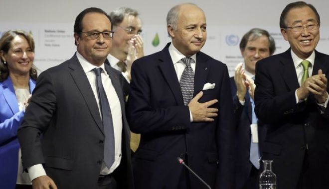 French Foreign Affairs Minister Laurent Fabius, center, President-designate of COP21, puts his hand over his heart after his speech as he stands near French President Francois Hollande, left, and United Nations Secretary-General Ban Ki-moon, right at the World Climate Change Conference 2015 (COP21) at Le Bourget, near Paris, France, Saturday, Dec. 12, 2015 . Negotiators from around the world appear to be closing in on a landmark accord to slow global warming, with a possible final draft to be presented Saturday for a last round of debate at talks outside Paris. (Philippe Wojazer/Pool Photo via AP)