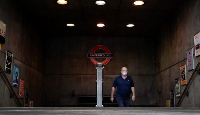 Κορονοϊός στη Βρετανία. Ένας άνδρας με μάσκα βγαίνει από το μετρό του Λονδίνου