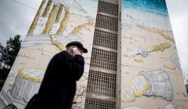 An elderly man talks on his cellphone as he walks past a mural depicting the Greek economy crisis covers a building housing student residences, in Thessaloniki, Greece on March 13, 2015. /                ,  ,   13 , 2015.