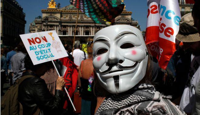"""Διαδηλωτής φορά τη μάσκα του προέδρου Εμανουέλ Μακρόν, στο """"πάρτι"""" για τον ένα χρόνο του στην προεδρία της Γαλλίας"""