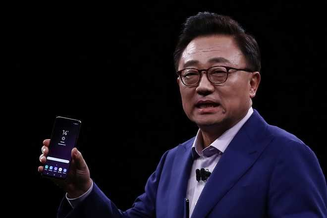 DJ Koh, Samsung's president and head of IT and Mobile Communications Divisions shows the new Galaxy S9, during a Samsung Galaxy Unpacked 2018 event on the eve of this week's Mobile World Congress wireless show, in Barcelona, Spain, Sunday, Feb 25, 2018. Samsung unveiled new smartphones with largely unchanged designs and incremental improvements such as a better camera. (AP Photo/Manu Fernandez)