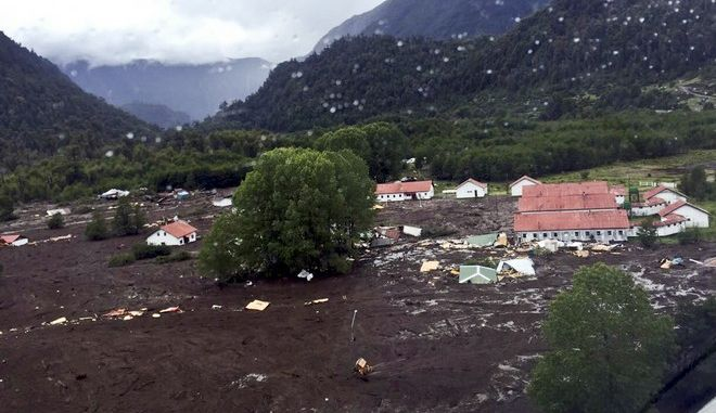 Mud covers Villa Santa Lucia in Chaiten, Chile, 1270 kilometers (790 miles) south of Santiago, on Saturday, Dec. 16, 2017. Officials said the deadly landslide occurred during a heavy rains. (Aton Chile via AP)