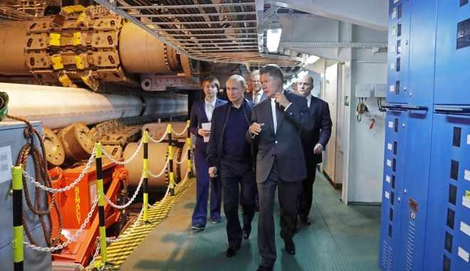 Russian President Vladimir Putin, second left, flanked by Gazprom CEO Alexei Miller, foreground right, visits the pipe laying vessel Pioneering Spirit in the Black Sea near Anapa, Russia, Friday, June 23, 2017. The president has inspected the work on the Turkish Stream gas pipeline project. (Mikhail Metzel/Sputnik, Kremlin Pool Photo via AP)