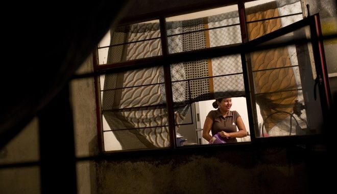 """In this June 27, 2017 photo, Emma Karina Cruz Velasquez, 16, of Honduras, prepares dinner for the household in the two-bedroom apartment shared by two refugee families headed by single mothers, in the Iztapalapa district of Mexico City. Laura Maria Cruz Martinez and another single mother fled Honduras with nine children in their care, when gang members threatened them hours after they reported to police that gangsters had been harassing her niece. They chose to settle in Mexico, since crossing the country and trying to enter the United States, risking deportation all along the way, seemed unnecessarily risky. As Emma explained: """"If they sent us back to our country it was certain death."""" (AP Photo/Rebecca Blackwell)"""