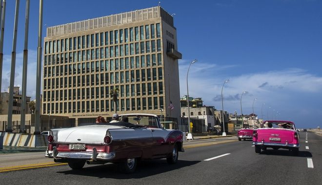 In this Oct. 3, 2017 photo, tourists ride classic convertible cars on the Malecon beside the United States Embassy in Havana, Cuba. Less than three years have passed since the longtime enemies began an ambitious diplomatic experiment, restoring formal ties despite lingering resentments and potent political opposition on both sides of the Florida Straits. Despite all that, a delicate detente took hold in 2015 and has slowly but steadily progressed. And now the experiment was upended when American embassy workers started falling ill last year in Havana, the unwitting victims of eerie, invisible attack.(AP Photo/Desmond Boylan)