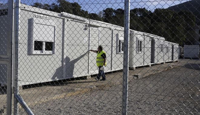 A worker closes the door of a container house at a registration and hospitality center, know as a hotspot, on the southeastern Greek island of Leros, Tuesday, Feb. 16, 2016. Greek Defense Minister Pannos Kammenos said that military teams have set up most of the long-delayed migrant reception facilities the country has promised its European Union partners to build. But he said the installations may not have to be fully used. (AP Photo/Petros Giannakouris)