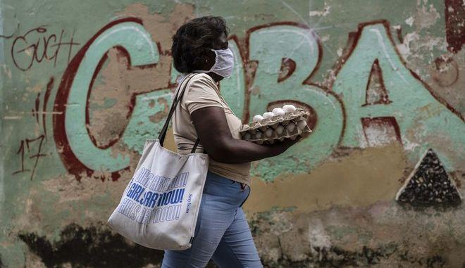 Γυναίκα με μάσκα περπατάει σε δρόμο της Κούβας