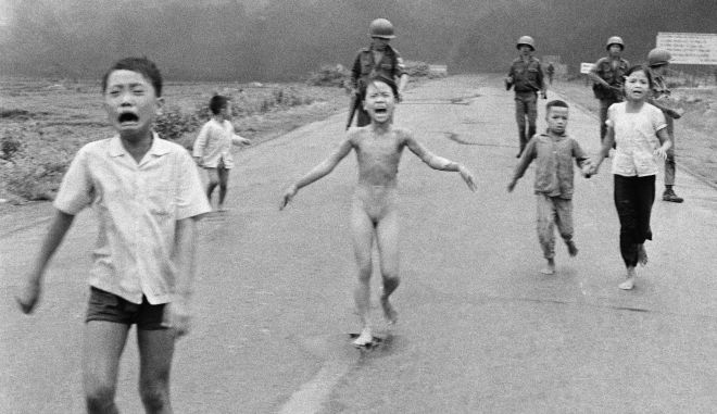 South Vietnamese forces follow after terrified children, including 9-year-old Kim Phuc, center, as they run down Route 1 near Trang Bang after an aerial napalm attack on suspected Viet Cong hiding places on June 8, 1972. A South Vietnamese plane accidentally dropped its flaming napalm on South Vietnamese troops and civilians. The terrified girl had ripped off her burning clothes while fleeing. The children from left to right are: Phan Thanh Tam, younger brother of Kim Phuc, who lost an eye, Phan Thanh Phouc, youngest brother of Kim Phuc, Kim Phuc, and Kim's cousins Ho Van Bon, and Ho Thi Ting. Behind them are soldiers of the Vietnam Army 25th Division. (AP Photo/Nick Ut)