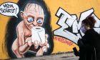 Γυναίκα μπροστά από γκράφιτι που απεικονίζει το Γκόλουμ με ένα ρολό χαρτί υγείας