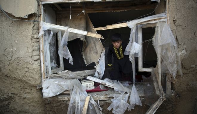 Ένα αγόρι στο παράθυρο ενός κατεστραμμένου σπιτιού στο Αφγανιστάν. (φώτο αρχείου)
