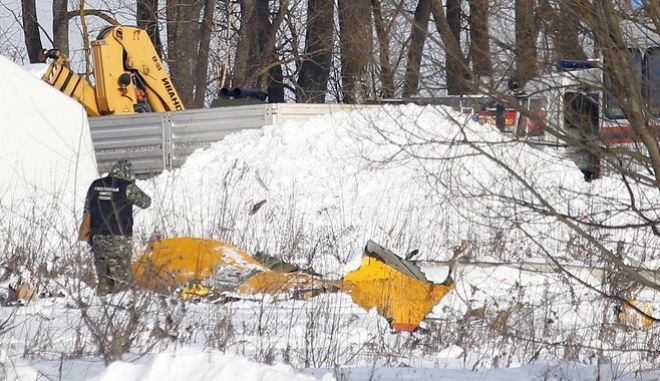 A man looks at wreckage near the scene of a AN-148 plane crash in Stepanovskoye village, about 40 kilometers (25 miles) from the Domodedovo airport, Russia, Moday, Feb. 12, 2018. A Russian passenger plane carrying 71 people crashed Sunday near Moscow, killing everyone aboard shortly after the jet took off from one of the city's airports. The Saratov Airlines regional jet disappeared from radar screens a few minutes after departing from Domodedovo Airport en route to Orsk, a city some 1,500 kilometers (1,000 miles) southeast of Moscow. (AP Photo/Alexander Zemlianichenko)