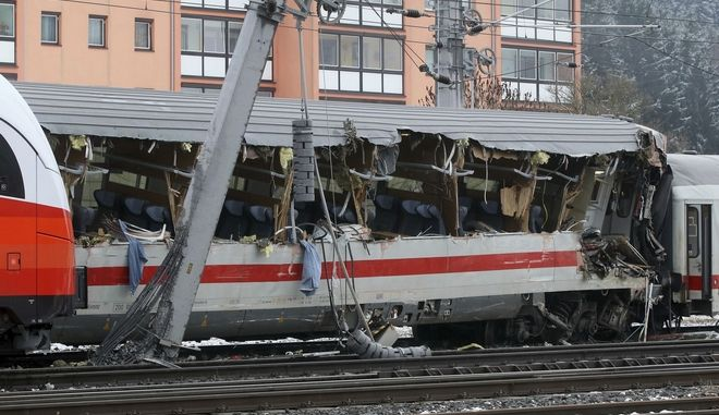 A destroyed carriage passenger car stands at the scene of a train crash in Niklasdorf, Austria, Monday, Feb. 12, 2018. Two passenger trains crashed in central Austria on Monday, killing one person and injuring 22 others, authorities said. One train hit the side of the other near the station in Niklasdorf, a town 60 kilometers (40 miles) north of Graz, said Graz police spokesman Leo Josefus. (AP Photo/Ronald Zak)