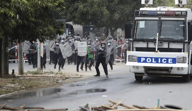 Police security forces advance forward during a security operation in Mandalay, Myanmar, Saturday, Feb. 20, 2021. Two anti-coup protesters were shot dead by riot police who fired live rounds Saturday in Mandalay, Myanmar's second-largest city, local media reported. (AP Photo)