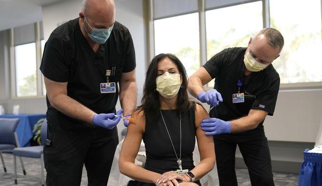 Η γιατρός Dr. Lilian Abbo, κάνει ταυτόχρονα εμβόλιο για τη γρίπη καθώς και εμβόλιο Pfizer COVID-19 στο Jackson Memorial Hospital