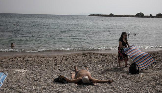 Άνδρας κάνει ηλιοθεραπεία σε παραλία της Γλυφάδας