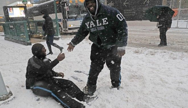 Marcus Greenaway, right, laughs as he helps his friend Psyquan Campbell up after Cambell slipped in the snow crossing a street in lower Manhattan in New York, Thursday, Jan. 4, 2018. A massive winter storm swept from the Carolinas to Maine on Thursday, dumping snow along the coast and bringing strong winds that will usher in possible record-breaking cold.(AP Photo/Kathy Willens)