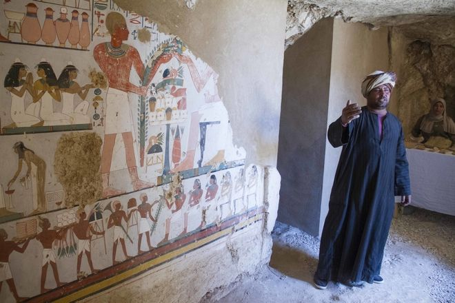 An Egyptian guard stands next to a funeral mural inside a newly discovered tomb on Luxor's West Bank known as