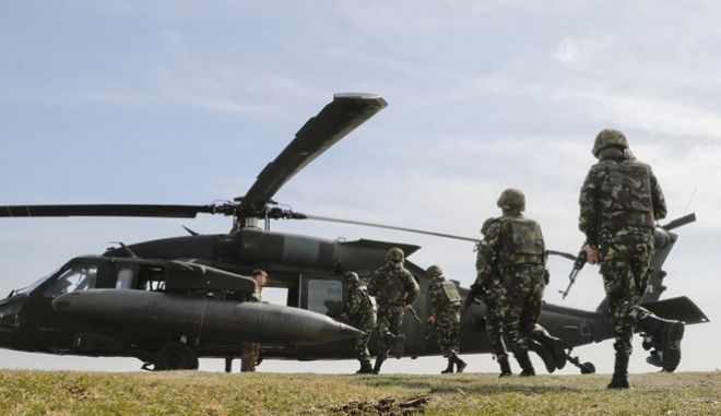 Romanian servicemen run to board an US Army 2nd Battalion, 10th Regiment, 10th Brigade UH-60 Blackhawk helicopter during a joint US-Romanian air assault exercise at the Mihail Kogalniceanu airbase, eastern Romania, Wednesday, March 8, 2017. Romanian and U.S troops are staging joint exercises with U.S. Black Hawk helicopters, part of the 10th Combat Aviation Brigade nine-month rotational deployment in support of Operation Atlantic Resolve, which aims to reassure NATO's European allies in light of Russia's invasion in Ukraine. (AP Photo/Vadim Ghirda)