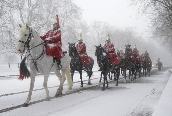 Members of the Household Cavalry return to their barracks as snow falls in London, Wednesday, Feb. 28, 2018. Britain, which is buffered by the Atlantic Ocean and tends to have temperate winters, saw heavy snow in some areas that disrupted road, rail and air travel and forced hundreds of schools to close. (AP Photo/Alastair Grant)