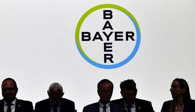 Μέλη του ΔΣ της Bayer μπροστά στο logo της εταιρείας