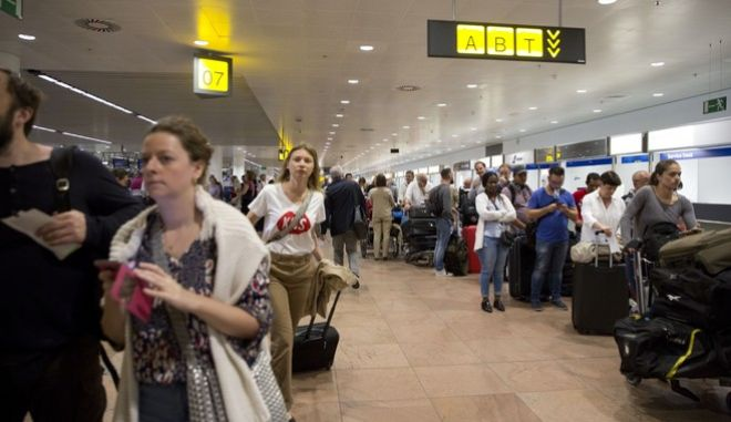 Passengers wait in long lines at Brussels Zaventem Airport in Brussels on Thursday, June 15, 2017. A power outage hit Brussels airport early Thursday, delaying departing planes and leaving hundreds of people stranded outside the terminal. (AP Photo/Virginia Mayo)