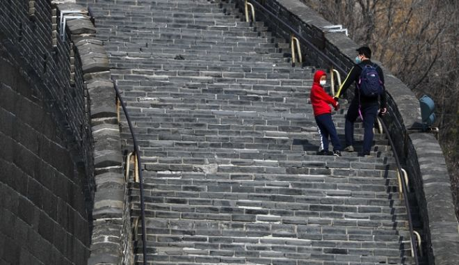 Άνδρας και παιδί με μάσκες στο Σινικό Τείχος