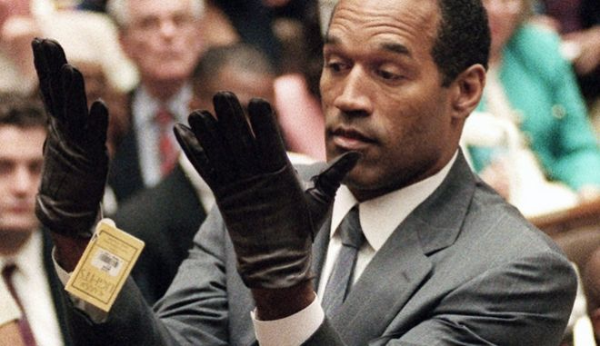 "FILE - In this June 21, 1995 file photo, O.J. Simpson holds up his hands before the jury after putting on a new pair of gloves similar to the infamous bloody gloves during his double-murder trial in Los Angeles. During Simpson's trial, a prosecutor famously asks him to put on a pair of gloves allegedly worn by the killer. The gloves appeared to be too tight, reinforcing the immortal words of defense attorney Johnnie Cochran: ""If it doesn't fit, you must acquit."" (AP Photo/Vince Bucci, Pool, File)"