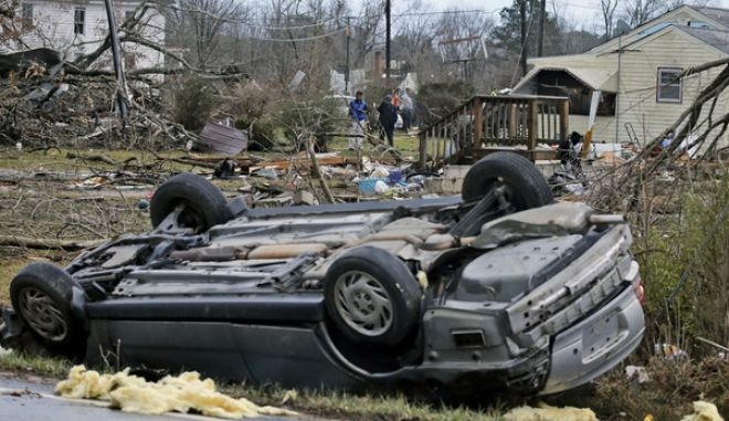 An overturned car rest on a highway next to the foundation of a mobile home that was throw across the highway by a deadly storm that swept through Waverly, Va., Wednesday, Feb. 24, 2016. (AP Photo/Steve Helber)