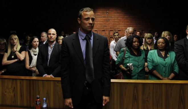 """Blade Runner"" Oscar Pistorius awaits the start of court proceedings in the Pretoria Magistrates court February 19, 2013. Pistorius, a double amputee who became one of the biggest names in world athletics, was applying for bail after being charged in court with shooting dead his girlfriend, 30-year-old model Reeva Steenkamp, in his Pretoria house. Standing behind Oscar (3rd L), wearing a scarf, is his sister Aimee and his brother Carl (4th L).  To his right in green, are members of the ANC Women's League. REUTERS/Siphiwe Sibeko (SOUTH AFRICA - Tags: CRIME LAW SPORT ATHLETICS TPX IMAGES OF THE DAY) - RTR3DZA7"